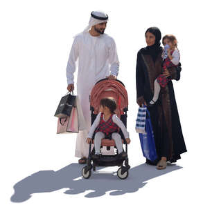 backlit arab family with shopping bags walking