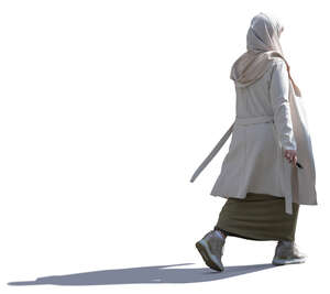 backlit muslim woman with a beige hijab walking