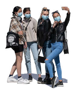 four girls with face masks standing and taking a selfie