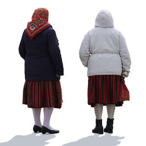 two backlit elderly women in ethnic clothing and winter jackets standing