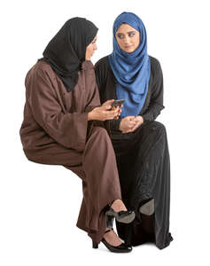 two muslim women sitting and talking