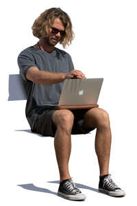 man sitting with a laptop on his knees