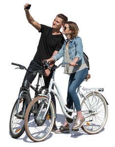 young man and woman stopping while biking to take a selfie