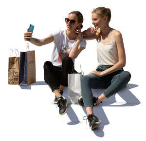 two young women sitting on stairs and taking a selfie