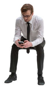 cut out businessman sitting and browsing his phone
