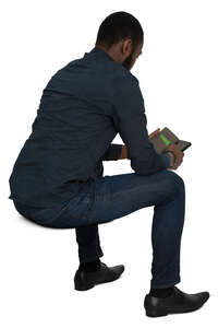 cut out black man sitting and checking his phone