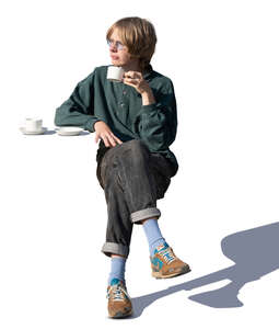 young man sitting in a cafe and drinking coffee