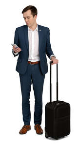 cut out young travelling businessman standing and looking at his phone