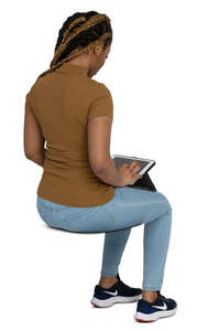cut out black woman sitting and looking smth at her ipad