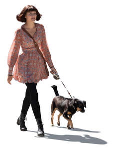 cut out young backlit woman walking a dog