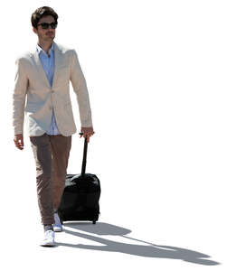 cut out backlit young man with a suitcase walking