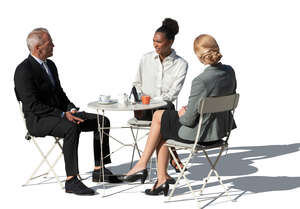 three cut out businesspeople sitting in a cafe and talking