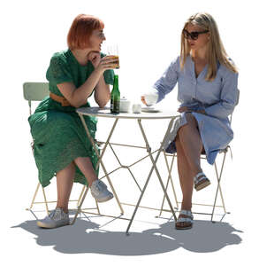 two cut out backlit young women sitting in a cafe and talking