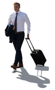 cut out backlit businessman walking and pulling a suitcase