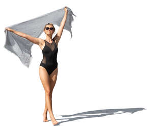 cut out woman in a black swimsuit holding a light towel walking on the beach