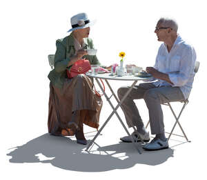 cut out backlit elderly couple sitting in a cafe
