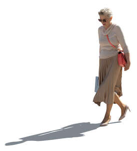 cut out backlit older woman with a shopping bag walking