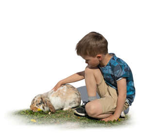 cut out boy sitting on the grass and petting a rabbit