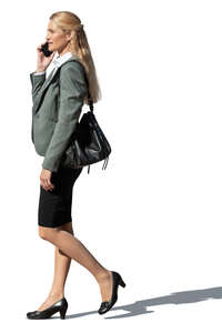 cut out businesswoman walking and talking on a phone