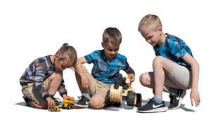 three cut out boys playing with toy cars