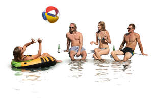cut out group of young people sitting by the pool and drinking and playing with a beach ball