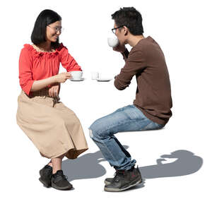 cut out asian man and woman sitting in a cafe and drinking coffee