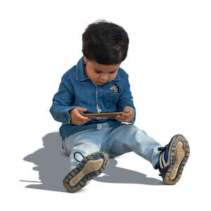 cut out little boy sitting on the ground with a smartphone in his hand