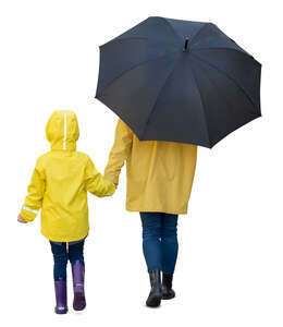 mother and daughter in yellow raincoats walking hand in hand on a rainy day