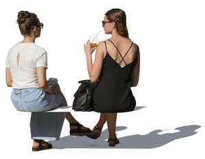 two cut out women sitting and drinking smoothies