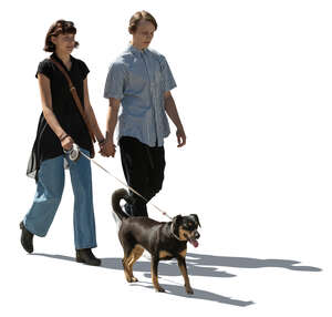 cut out young backlit couple with a dog walking hand in hand