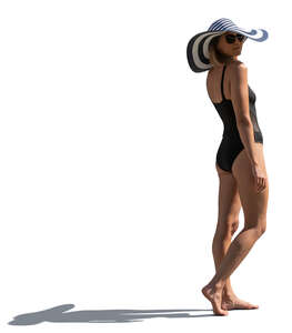 sidelit woman in a swimsuit and wearing a big summer hat standing