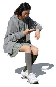 cut out woman sitting at a table and looking at her phone