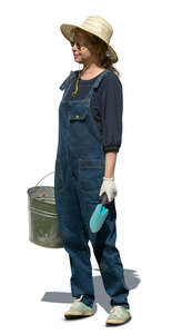 cut out garden worker in denim ovaralls and holding a bucket standing