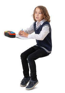 cut out schoolboy sitting at a desk and writing