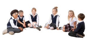 six cut out schoolchildren sitting on the ground in a circle
