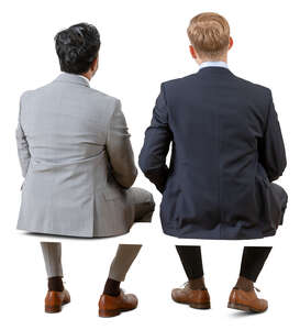 two cut out businessmen sitting seen from behind