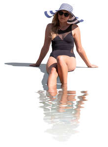 cut out woman sitting at the edge of the pool with her legs in the water