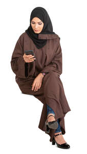 cut out muslim woman in a brown abaya sitting