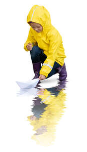 cut out little girl in a yellow raincoat floating a paper boat
