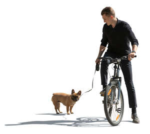 sidelit man with a dog riding a bike