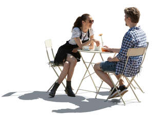 backlit image of a cafe table with man an woman sitting and talking