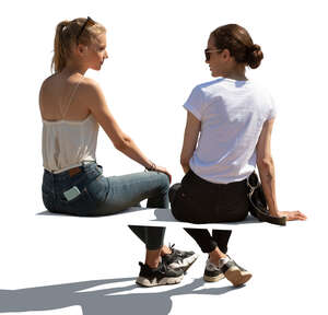 two cut out  women sitting and talking seen from behind