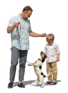 cut out father and son standing and playing with a dog