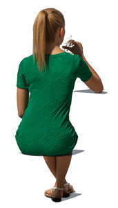 cut out woman in a green dress sitting and drinking water