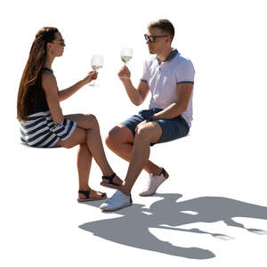 cut out backlit man and woman sitting in a cafe and drinking wine