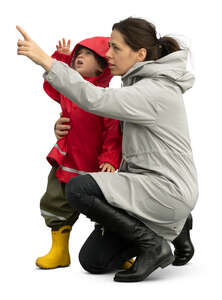 cut out woman with small child squatting and pointing at smth