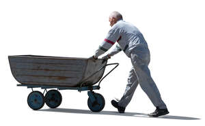 cut out older man pushing a large wheelbarrow