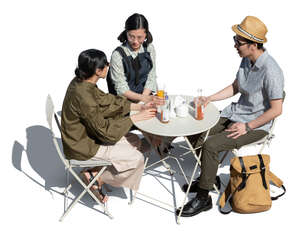 three cut out young people sitting in a cafe seen from above