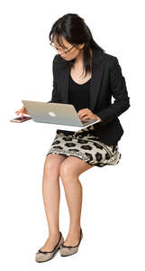 cut out asian woman sitting at a desk and working