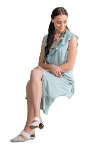 cut out woman in a pale blue dress sitting
